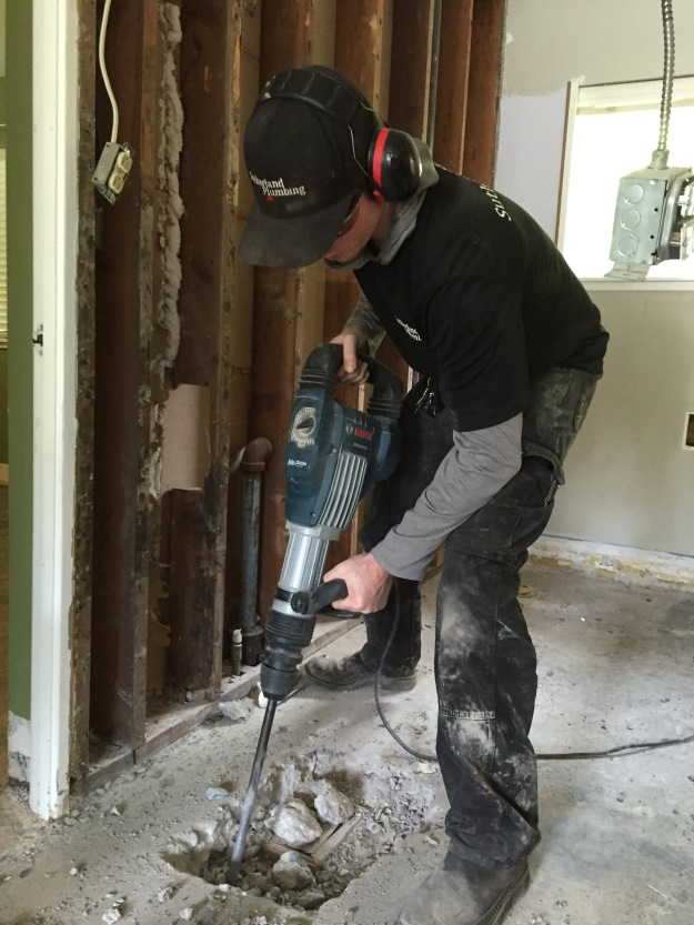 Sean Anderson earning his keep, jack-hammering through a concrete bathroom floor to repair drain(s).