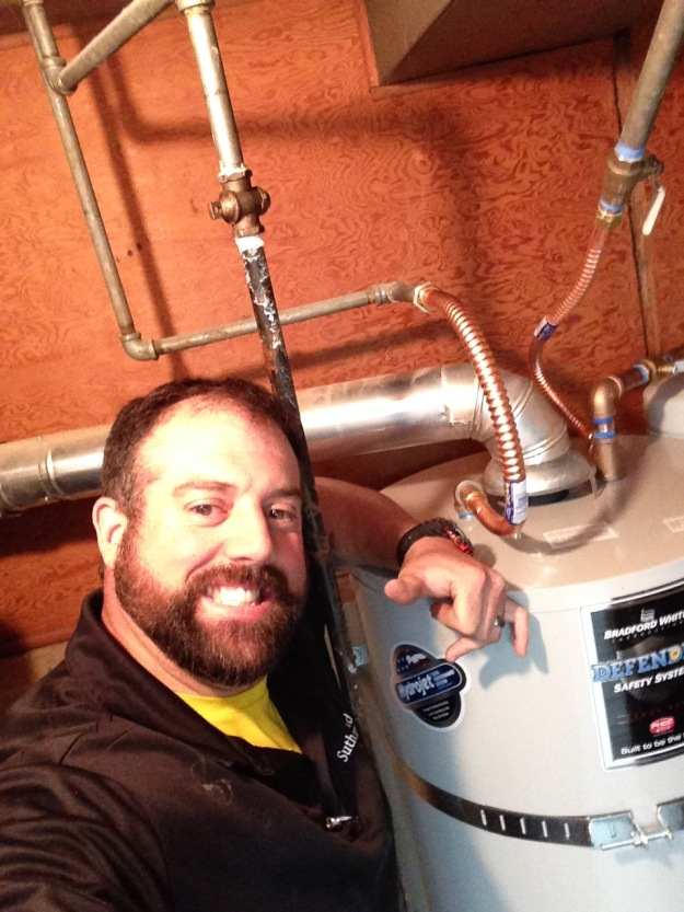 John Benton with one of his newly installed 50 gallon gas water heaters.