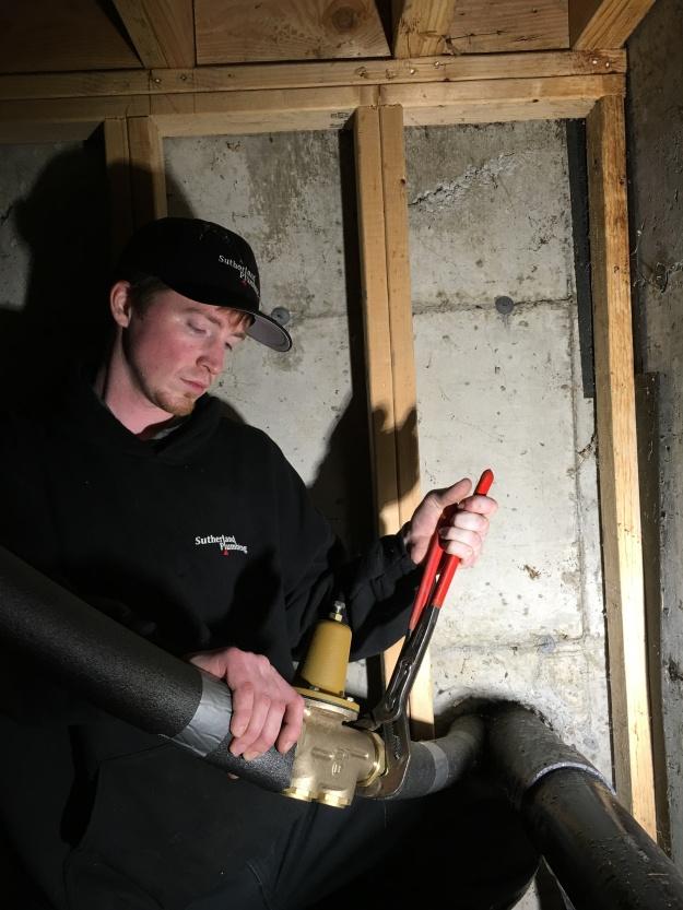 "Sutherland Plumbing's Sean Anderson installing a 1-1/4"" Pressure Reducing Valve."